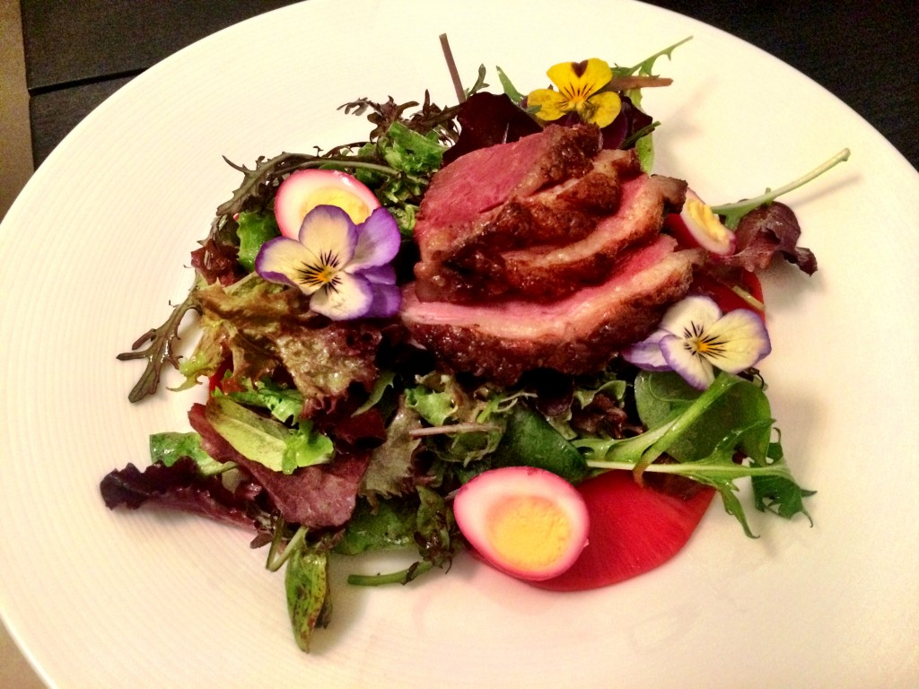 Slice and fan the duck onto the salad. Garnish with quail eggs and edible Spring flowers. (link to full recipe below)